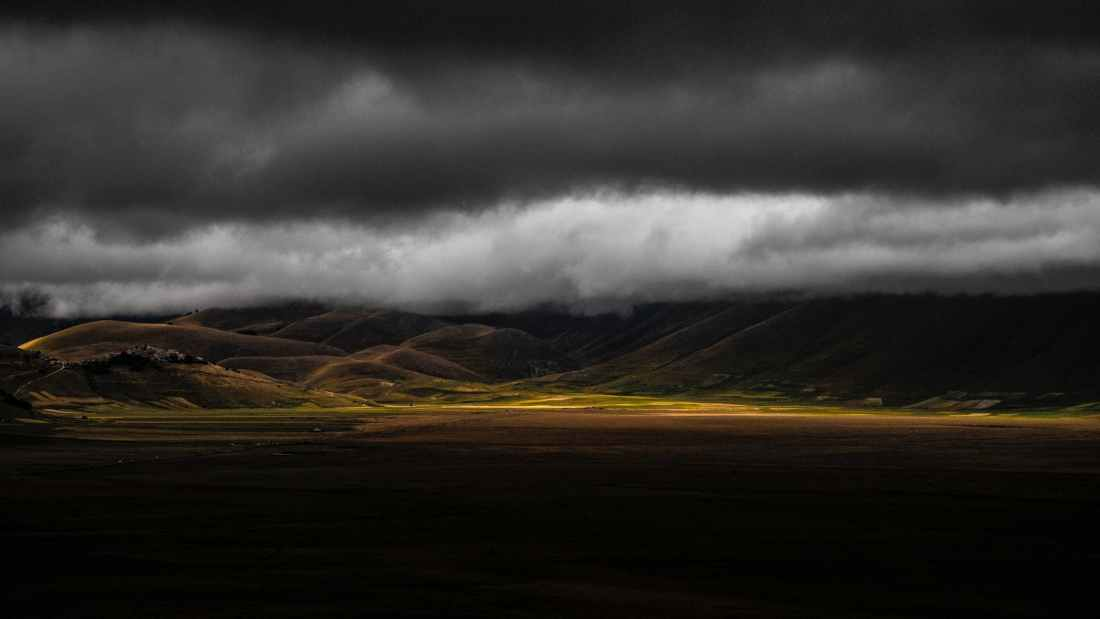 scenic view of mountains under cloudy sky